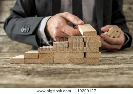 Front Closeup View Of Businessman Constructing Steps Of Wooden Pegs
