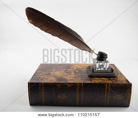 Ancient Ink Pot With Quill On Old Tome