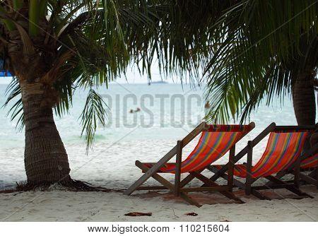 Two Beach Chairs On A Beach Under Palm-trees Near The Sea