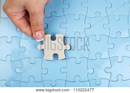 Person fitting the last puzzle piece.Concept image of building and button up.