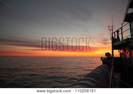 Ship's Bridge Wing With Searchlight Silhouette Against Rising Sun