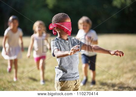 Group of children plays blind man's buff at the park in summer
