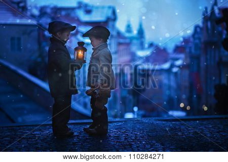 Silhouettes Of Two Kids, Standing On A Stairs, Holding A Lantern, View Of Prague Behind Them