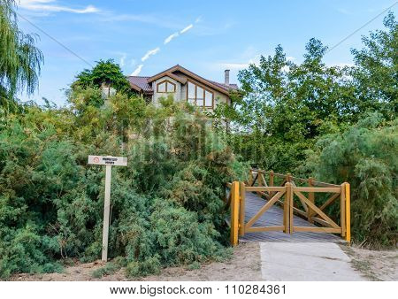 Newly Built House In The Middle Of The Woods Surrounded By Fence. Horizontal View Of A Building In W