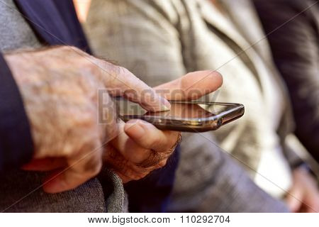closeup of an old caucasian man using a smartphone outdoors