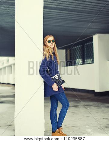 Pretty Blonde Woman Wearing A Jacket And Sunglasses With Retro Camera In City