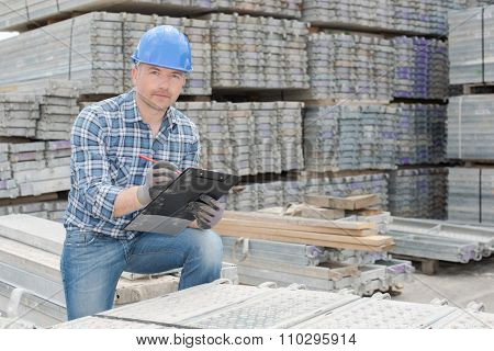 Workman stood with cast concrete slabs