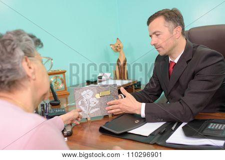 Undertaker showing memorial plaque to elderly lady