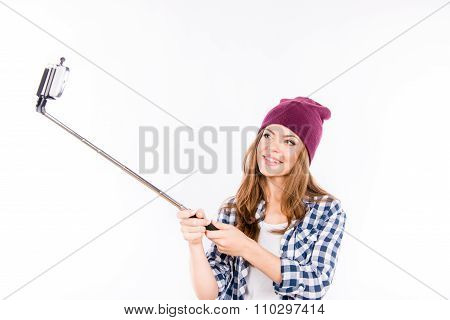 Happy Beautiful Girl In A Hipster Hat Making Selfe Photo On The Phone With Selfe Stick