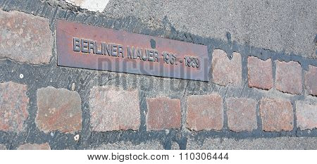 Sign on the road to show the place of the old Berlin Wall.