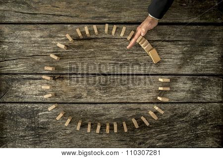 Businessman Stopping Falling Dominos Placed In A Circle With His Hand