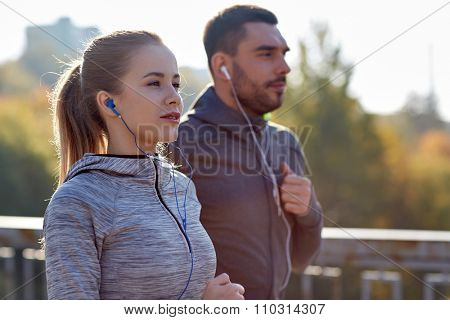 fitness, sport, people, technology and lifestyle concept - happy couple running and listening to music in earphones at city