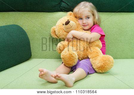 Little Girl Hugging A Teddy Bear.
