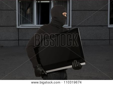 Thief with balaclava stealing computer monitor or television  poster