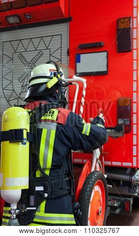 A fireman with breathing apparatus and mask on the fire truck