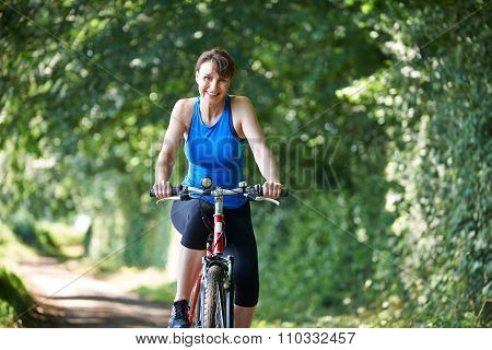 Middle Aged Woman Riding Bike Through Countryside