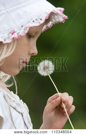 Girl With Dandelion On Blurred Background