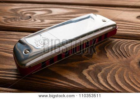 Harmonica On Wooden Background Closeup