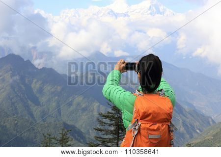 young woman backpacker hiking on mountian peak