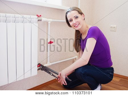 Beautiful, Young Woman  Sets Up The Radiator Heating