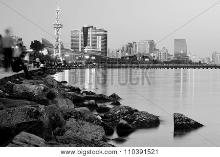 Baku Bulvar from shore at night with lights and boy looking out to sea