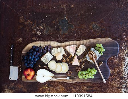 Wine appetizers set: French cheese selection, honeycomb, grapes, peach and walnuts on rustic wooden
