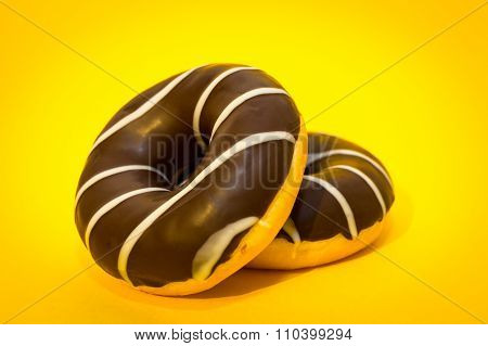 Two chocolate donuts on the yellow background