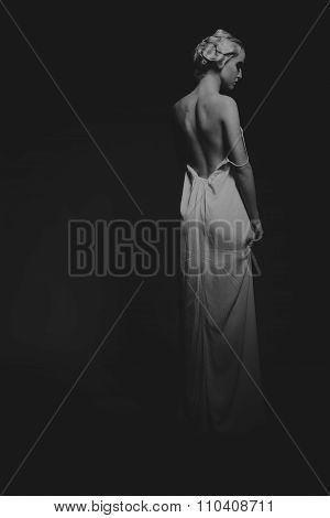 Sexy blonde in white dress on a dark background