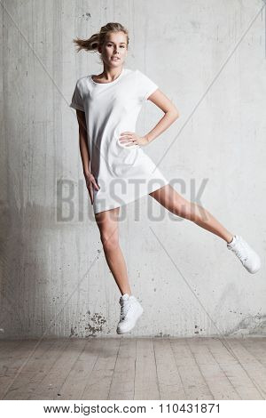Girl With A Smile Wearing A White T-shirt Jumps
