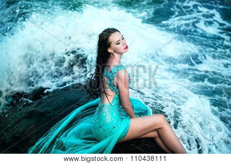 Woman posing on a beach with rocks