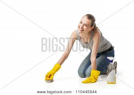 woman in rubber glover with brush cleaning floor