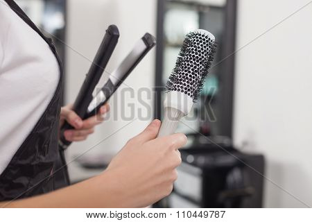 Cheerful female hairstylist is working in beauty salon