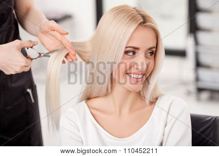 Professional hairdresser is making haircut for girl