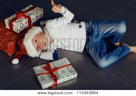 Christmas Photo Of  Little Boy In Santa Hat And Jeans Smiling With  Christmas Gifts
