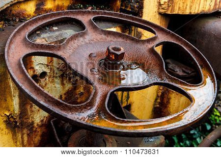 Close Up Of Rust Wheel On Yellow Freight Train Car.