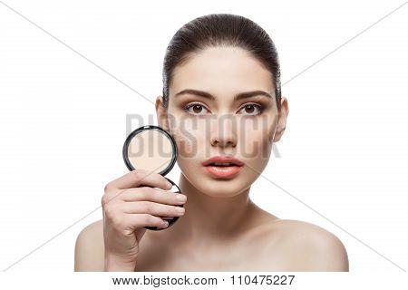 Beautiful girl holding pressed powder