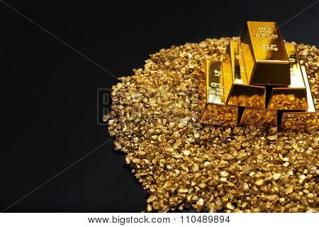 Gold bars and nugget grains, on grey background