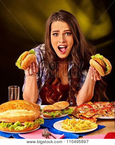 Girl eat fastfood big hamburger and pizza .