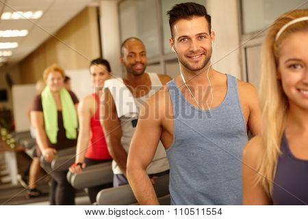 Handsome man smiling in gym with earbuds, training among others.