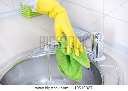 Close up of female hands with rubber gloves cleaning kitchen sink and faucet poster