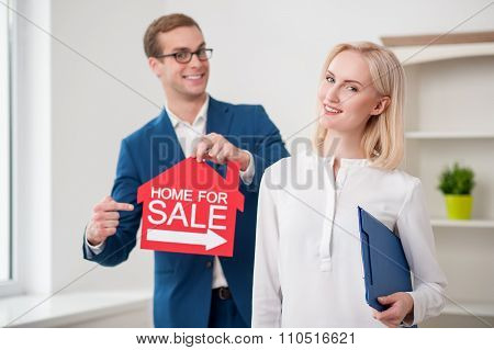 Cheerful estate agent is proposing to buy an apartment