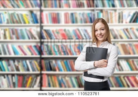 Young Woman Standing, Holding Notebook In Front Of Book Shelves
