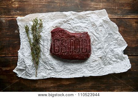 Piece Of Steak Meat On Craft Paper With Romero Top View