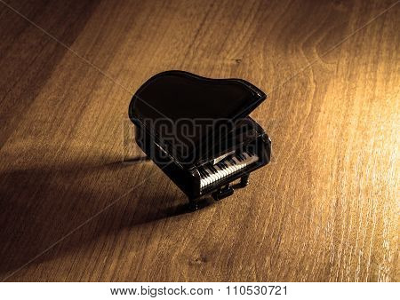 Miniature Model Of Black Grand Piano With Shadow On Wooden Table