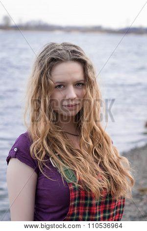 Beautiful girl in checkered dress near river