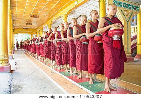 BAGO, MYANMAR -November 26, 2015: Monks going for lunch in the monastery at Bago Myanmar. Buddhism in Myanmar is predominantly of the Theravada tradition, practised by 89% of the country's population