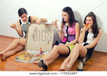 Cross Processed Image Of Three Beautiful Young Ladies Eating Pizza While Sitting On The Floor