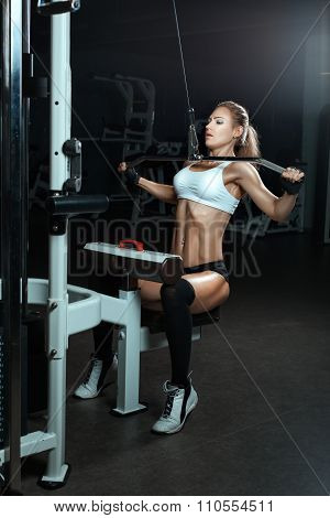 Woman Shakes Her Muscles On Simulator In The Gym.