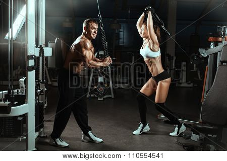 Man And A Woman Trained Muscles In The Gym.