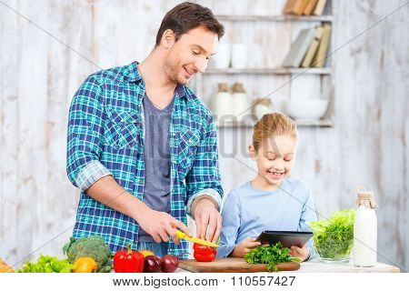 Happy father and daughter cooking together